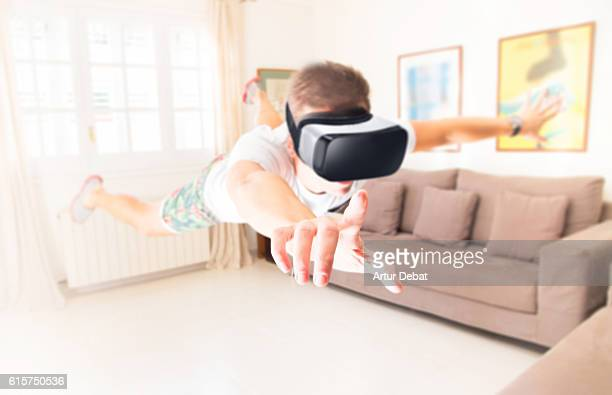 Guy levitating in the bright home living room experiencing the new technology using the virtual reality headsets transported and immerse in to another world. The VR headsets is the future of social communication and entertainment.