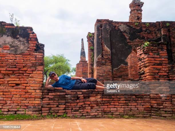 A guy lying on brick wall