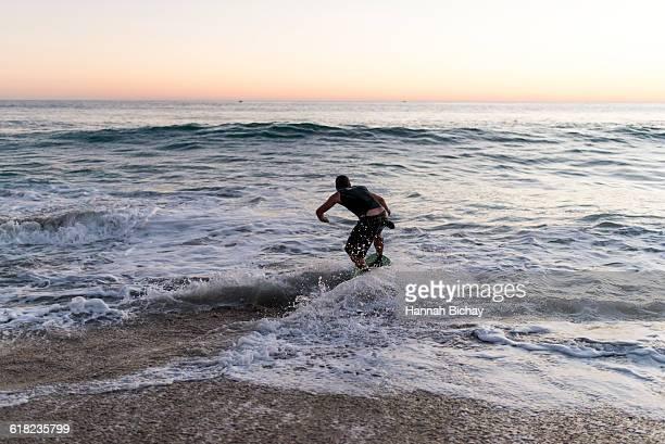 Guy on a skim board in the sea/beach