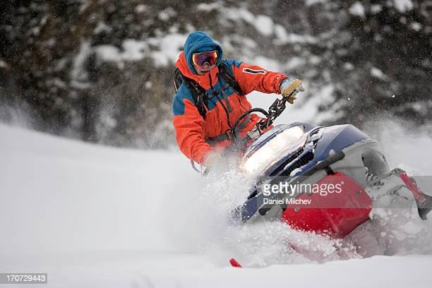 guy on a snowmobile taking a powder turn. - snowmobiling - fotografias e filmes do acervo