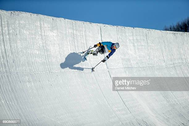 Guy on a wheelchair sled riding a super pipe.