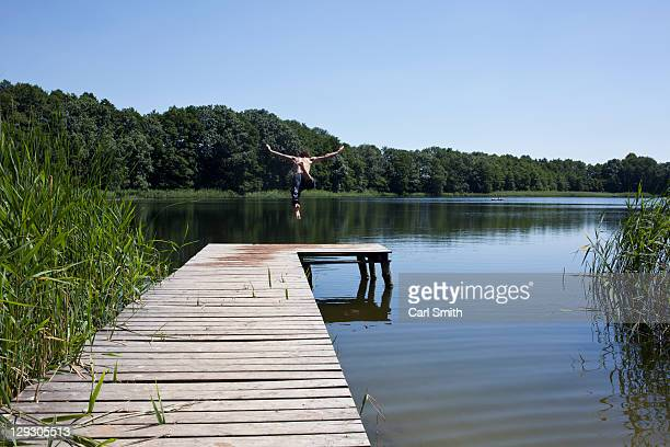 Guy on jetty dives into lake with arms outstretched