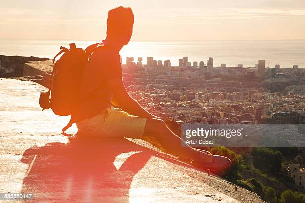 Guy on viewpoint contemplating Barcelona city.