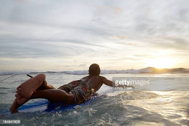 Guy paddling on surfboard into sunset