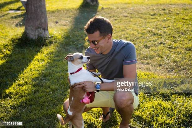 guy playing with dog during walk in public park. - collar stock pictures, royalty-free photos & images