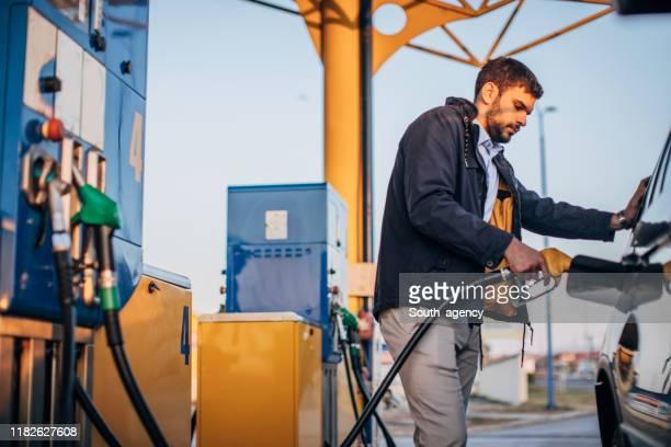guy pouring fuel in car - abastecer imagens e fotografias de stock