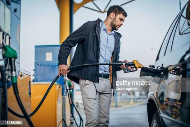 ガソリンスタンドで車に燃料を注ぐ男 - ガソリン ストックフォトと画像