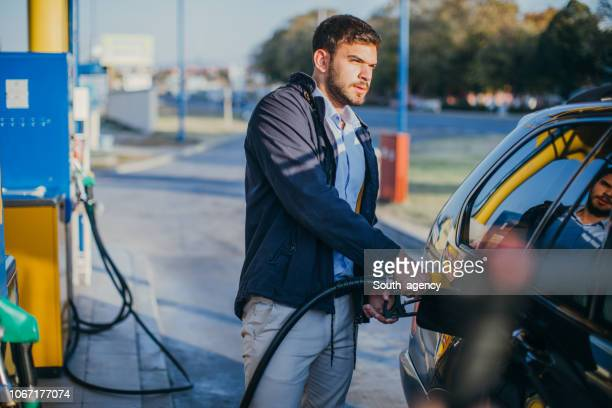 guy pouring fuel in vehicle - station stock pictures, royalty-free photos & images