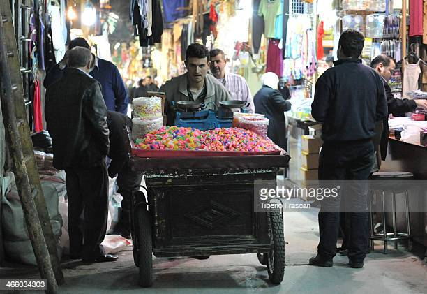 CONTENT] Guy pushing a cart full of colorful sweets in Damascus bazaar interior
