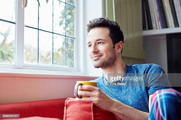 Guy relaxes on sofa looking out of window