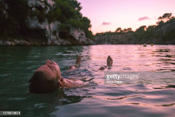 guy relaxing and floating in the sea water during sunset in the island of mallorca. - majorca stock pictures, royalty-free photos & images