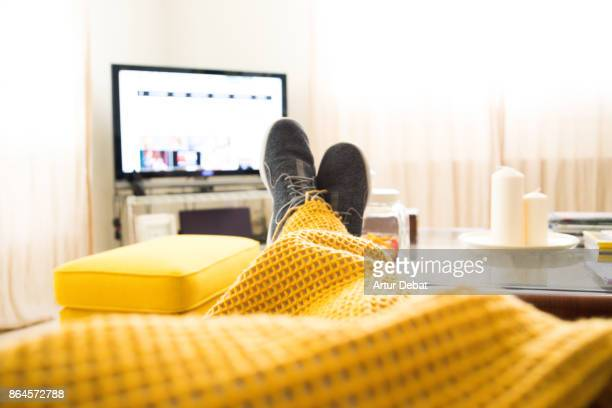 guy relaxing at home from personal perspective laying in sofa in autumn day covering with blanket while watching television. - laziness stock pictures, royalty-free photos & images