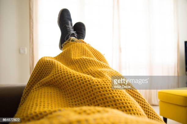 Guy relaxing at home from personal perspective laying in sofa in autumn day covering with blanket while watching television.