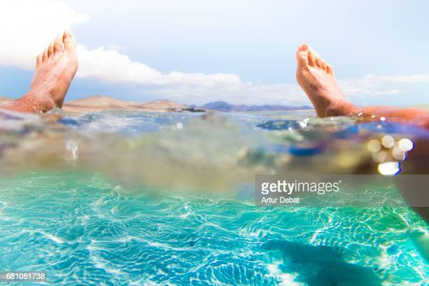 Guy resting on water from personal perspective in the stunning lagoon beach with turquoise and crystal waters in the south of Fuerteventura island during travel vacations in the island.
