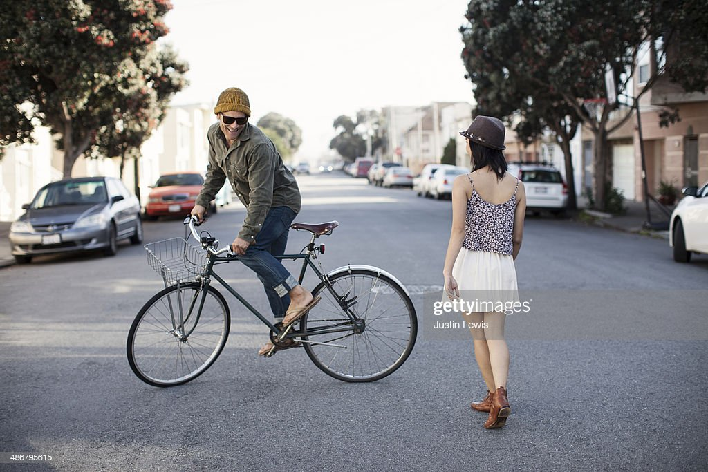 Guy riding circles around girl on bicycle : Stock Photo