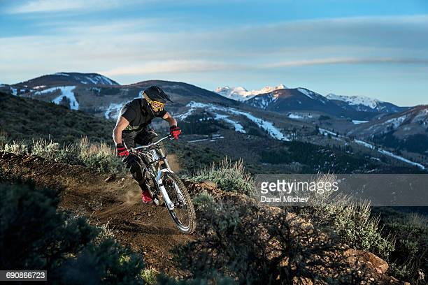 Guy riding mountain bike at sunrise