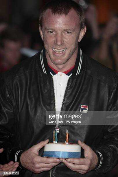 Guy Ritchie holds a birthday cake given to him by a photographer to celebrate his 41st birthday as he arrived at the UK premier of Nick Love's film...