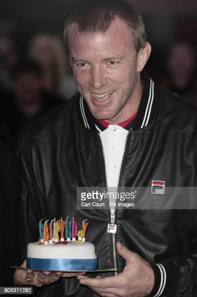 Guy Ritchie holds a birthday cake given to him by a photographer to celebrate his 41st birthday as he arrived at the UK premiere of Nick Love's film...