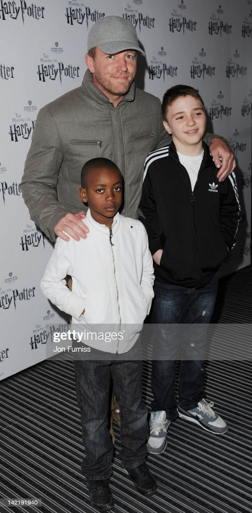Guy Ritchie (C) with David Banda (L) and Rocco Ritchie (R) attend the grand opening of Warner Bros Studio Tour London at Leavesden Studios on March 31, 2012 in Watford, England.