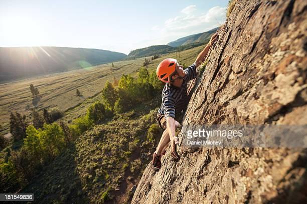 guy rock climbing at sunset. - rock climbing stock pictures, royalty-free photos & images