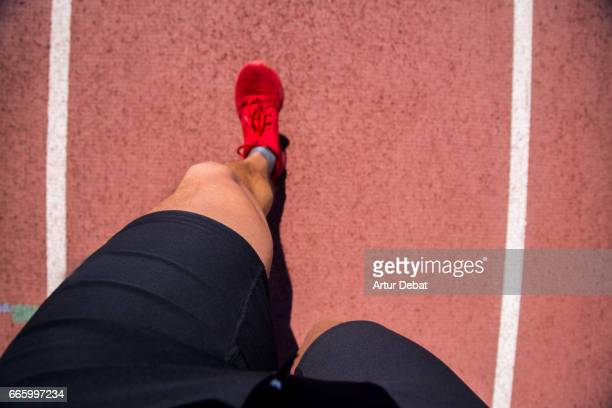 Guy running doing healthy outdoor sport routine in the athletics track, taken the picture from personal perspective looking down with legs, red shoes, and ground.