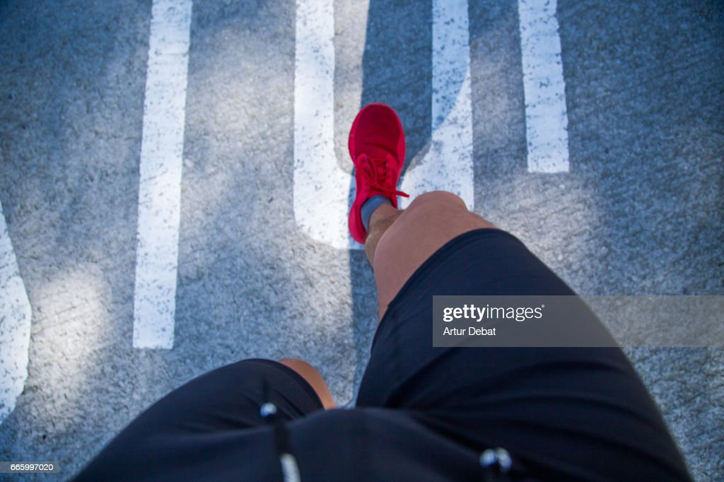 Guy running doing healthy outdoor sport routine in the city, taken the picture from personal perspective looking down with legs, red shoes, and ground. : Stock Photo