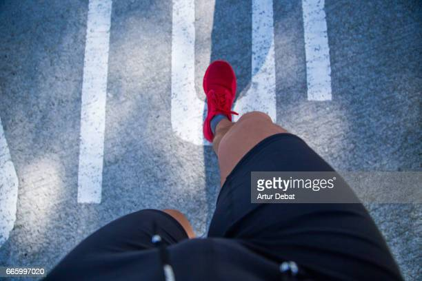 guy running doing healthy outdoor sport routine in the city, taken the picture from personal perspective looking down with legs, red shoes, and ground. - ponto de vista - fotografias e filmes do acervo