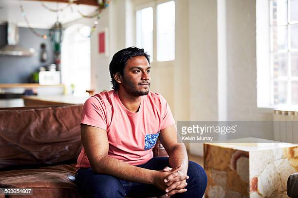 A guy sits on a sofa in his modern apartment