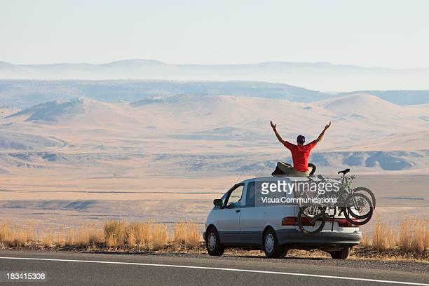 Mann sitzt auf dem Dach des Auto.