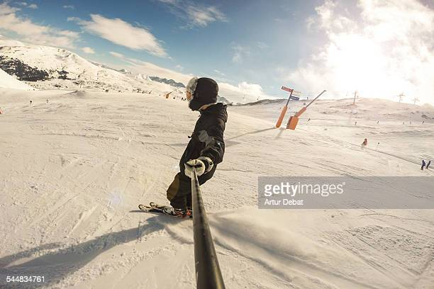 Guy skiing and taking a selfie with selfie stick
