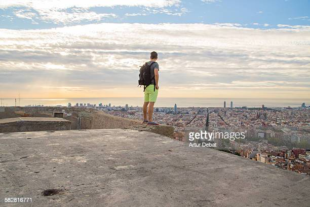 Guy standing up with the Barcelona city views.