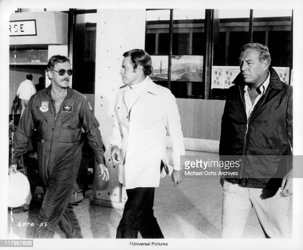 Guy Stockwell in a pilot outfit walking with Charlton Heston and George Kennedy in a scene from the film 'Airport' 1970