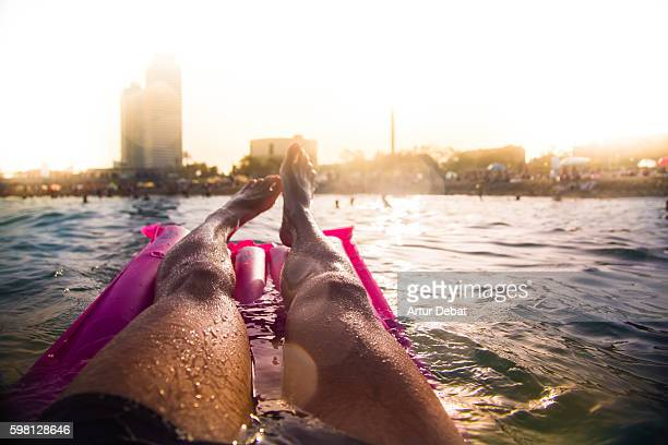 Guy swimming on pink inflatable bed pad on Mediterranean Sea from personal perspective with the skyline of the Barcelona city on sunset during summer time without stress and relaxing times.