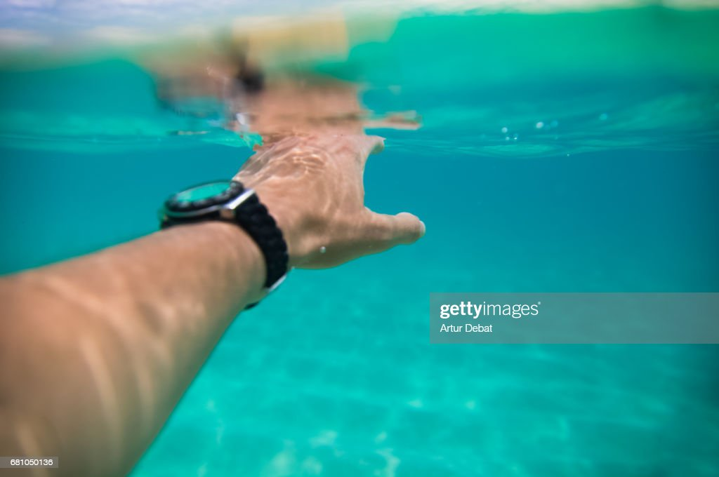 Guy swimming under water from personal perspective in a stunning nice clear water beach in Fuerteventura island during travel vacations with warm and sunny days. : Stock Photo