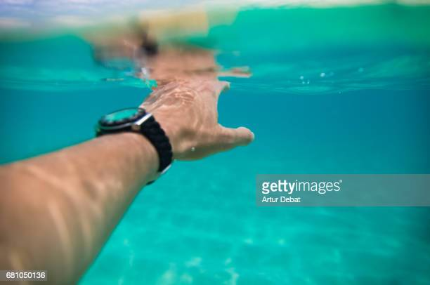 Guy swimming under water from personal perspective in a stunning nice clear water beach in Fuerteventura island during travel vacations with warm and sunny days.