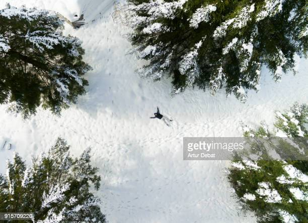 Guy taking a original selfie laying on the fresh snow with picture taken from drone directly from above with nice winter landscape.