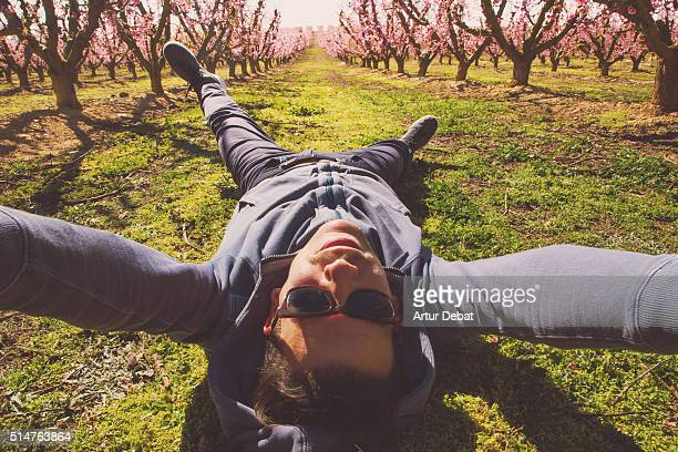Guy taking a original selfie with the beautiful landscape view of the blooming trees in springtime with pink flowers covering  the dry plane region of Lleida, in Catalonia.