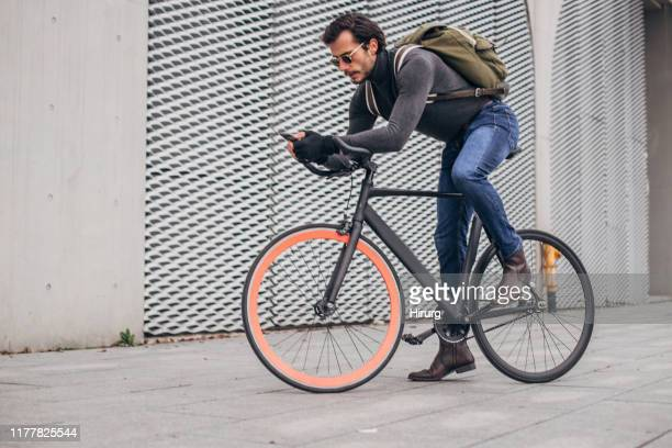 guy text messaging on a bicycle - dolcevita foto e immagini stock