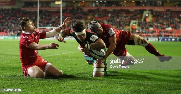 Guy Thompson of Leicester Tigers dives over for a first half try despite being held by Jonathan Davies and Steff Evans during the Champions Cup match...