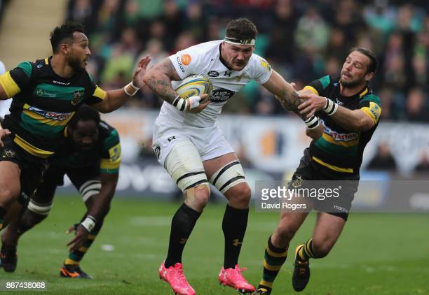 Guy Thompson of Wasps is tackled by Ben Foden and Nafi Tuitavake during the Aviva Premiership match between Northampton Saints and Wasps at...