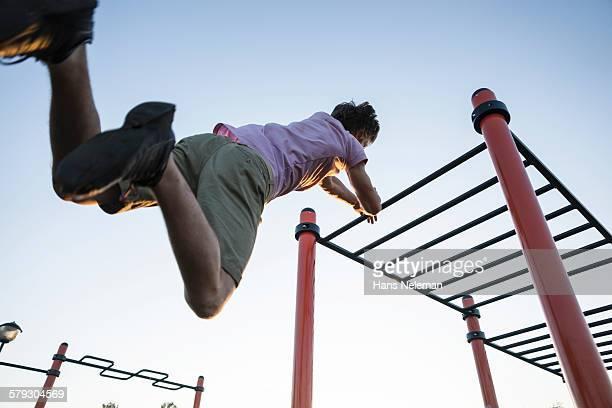 Guy training in park on monkey bars