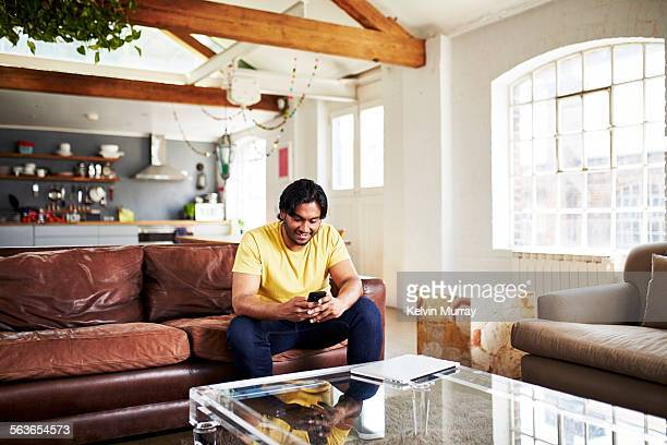 A guy uses his mobile phone whilst sitting on sofa
