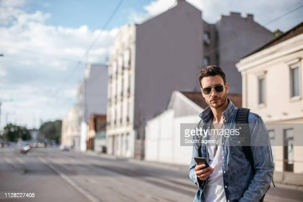 chico con móvil en la calle - un solo hombre joven fotografías e imágenes de stock