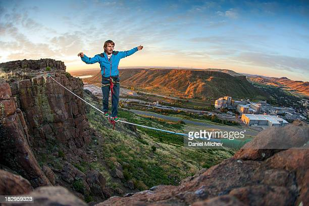 Guy walking on a rope at sunrise.