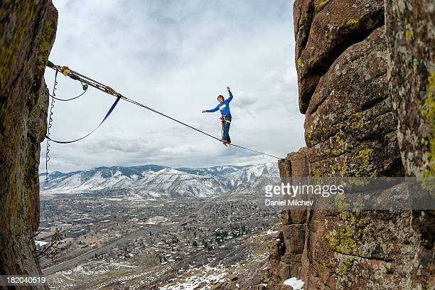 Guy walking on a rope over a town.