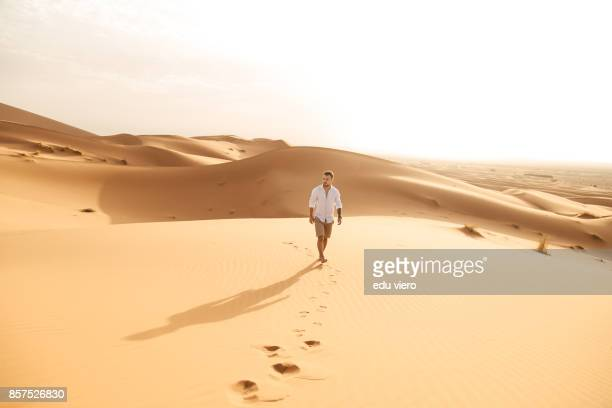 a guy walking on the desert - merzouga stock pictures, royalty-free photos & images