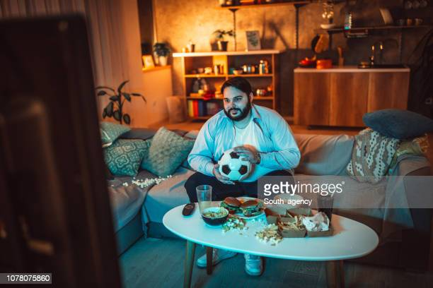 guy watching a soccer match - man cave stock pictures, royalty-free photos & images