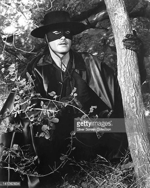 Guy Williams US actor in costume with an eye mask posing in foliage beside a tree trunk in an image issued as publicity for the US television series...