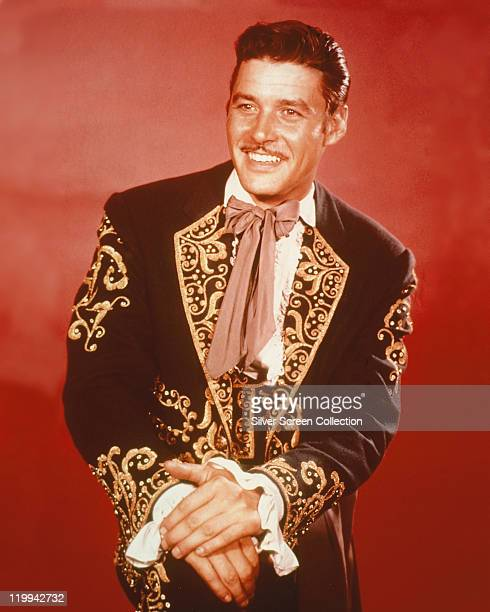 Guy Williams US actor wearing a mariachi costume and smiling in a studio portrait against a red background issued as publicity for the US television...