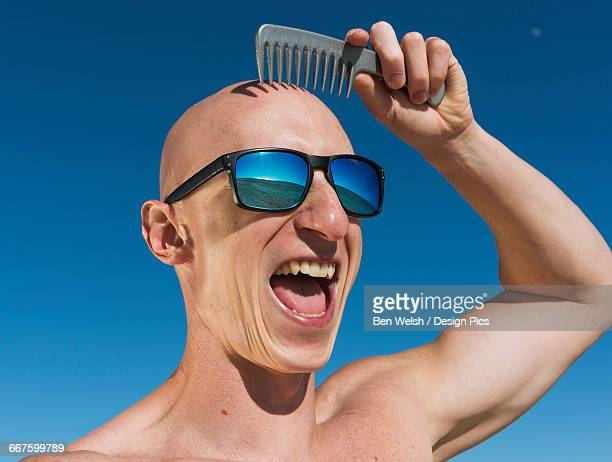 A guy with a bald head holds a comb over his hairless head while wearing sunglasses and a big smile